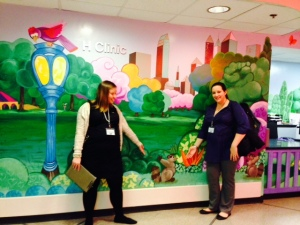 ALSAC Goddesses Laura and Nicole show off one of their favorite walls of the hospital, and their little racoon friend!